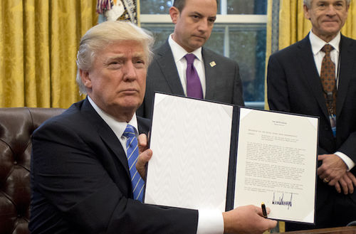 Sitting at his desk, Donald Trump holds up an executive order he signed on his first full day as president