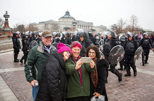 White people take photo with police wearing riot gear in the background
