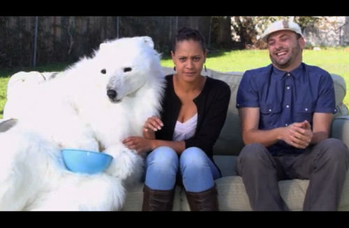 Person in White polar bear costume next to Brown woman in white shirt with black sweater and blue jeans next to White man in blue shirt with grey cap and grey pants, all on grey couch against green grass