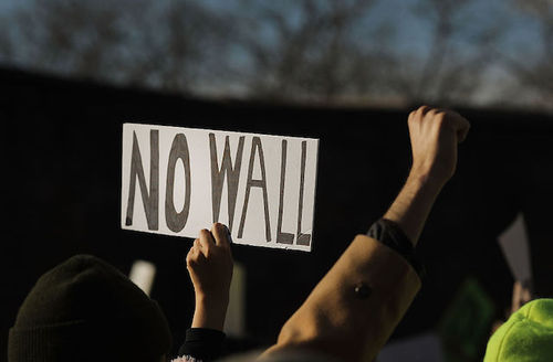 """Peole with fists in the air, said that says, """"No wall."""""""
