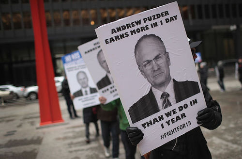 """Protestor holds sign that says, """"Andrew Puzder earns more in one day, than we do in one year. #FightFor15."""""""