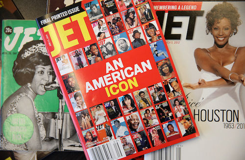 Green cover with white text and black-and-white photo next to red magazine with multicolored photos next to grey magazine with photo of Black woman in white dress and black text