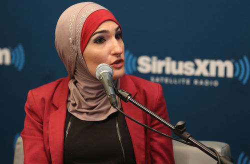 Brown woman in pink hijab with red blazer and brown shirt sits behind black microphone with grey head on grey chair in front of blue screen