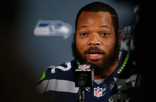 Black man in navy, green and grey uniform speaks into black microphone against blue background with gray, blue and green team logo