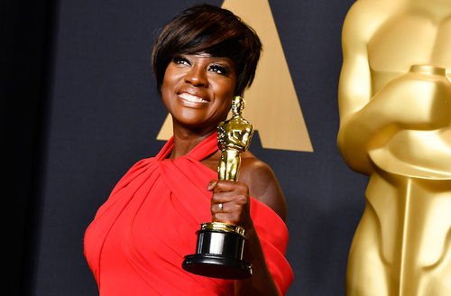 Black woman holds gold statue while wearing red dress in front of navy, black and gold background