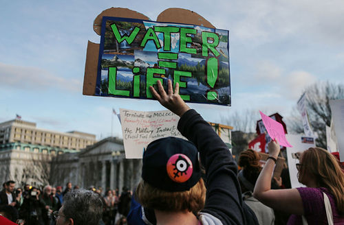 """A demonstrator holds a sign reading """"Water = Life!"""" at a demonstration outside the White House against President Donald Trump's executive action to allow the Dakota Access Pipeline on February 8, 2017, in Washington, D.C."""