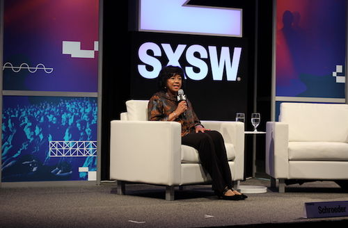 Black woman in brown blouse and black pants seated in off-white chair on black stage in front of purple, pink and blue background with white text and symbol