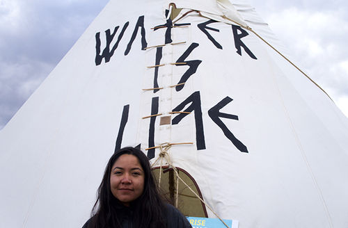 """Eva Cardenas stands before a tipi that reads, """"Water is life,"""" at the National Mall on March 10, 2017."""