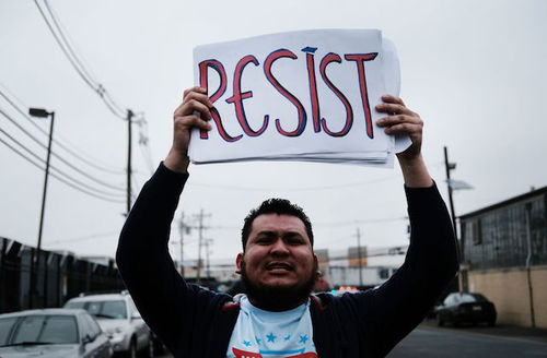 "Man holds sign that reads, ""Resist."""