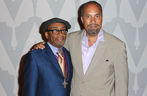 Black man in grey derby cap, gold tie navy suit next to Black man in brown suit and purple shirt in front of grey background