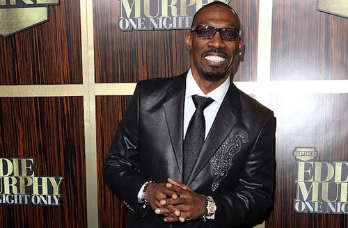 Black man in black sunglasses and black leather suit with white shirt and embroidering in front of brown wood wall with gold and white text