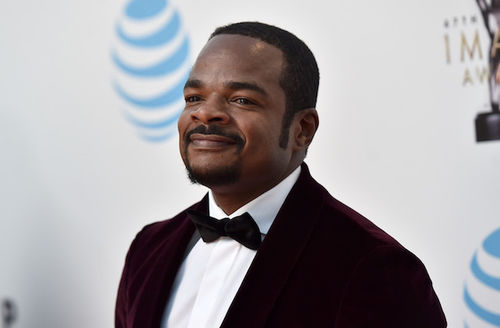Black man in brown tuxedo with white shirt in front of grey background with blue and gold logos
