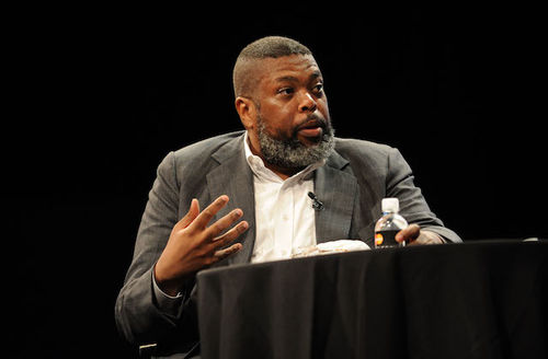 Black man seated in grey suit with white shirt at black table in front of black screen