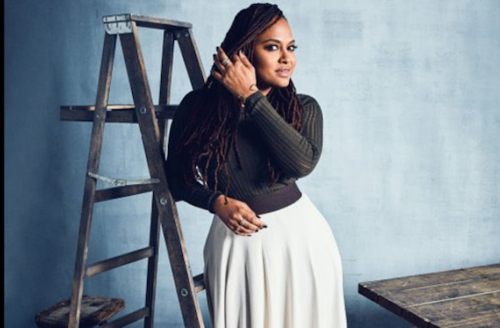 Black woman in black sweater stands against brown ladder and blue background