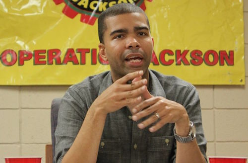 Black man in grey shirt seated in front of yellow wall with black, red and yellow banner