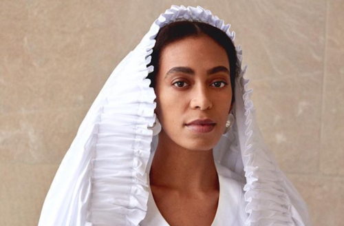 Black woman in white veil and shirt in front of brown background