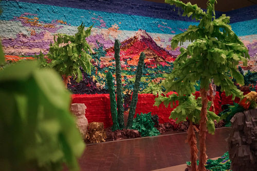 A wall decorated with colorful cut paper, resembling a landscape painting. Trees and other greenery in the foreground made of cardboard and paper.