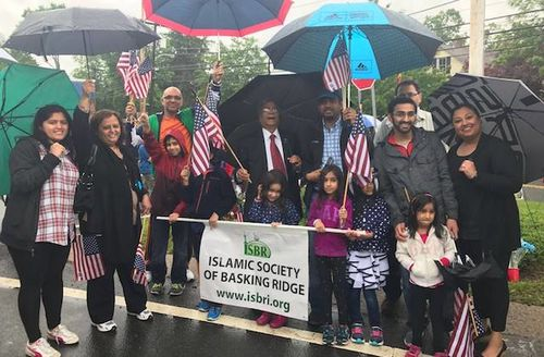 "Smiling group of people waving flags with sign that reads ""Islamic Society of Basking Ridge"""