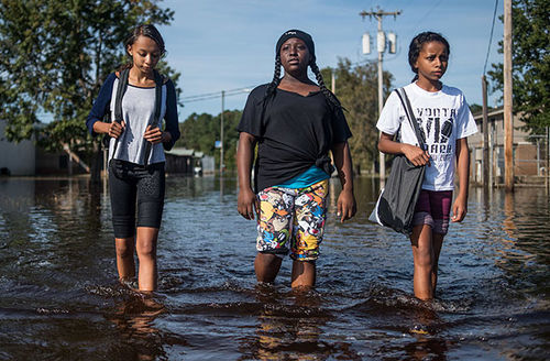 Cassandra Rush, Anyah Carpenter, and Rosa Rush walk through floodwaters in their neighborhood on October 15, 2016, in Lumberton, North Carolina. The town still needs $7 million  for clean up.