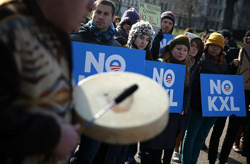 Activists hold signs as they protest in front of the White House against the Keystone XL pipeline January 13, 2015, in Washington, D.C.