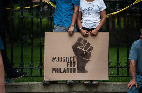 Brown couple hold brown sign with black image and text in front of green lawn and black fence and yellow police tape while on grey stone ledge