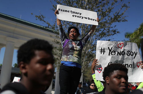 "Woman, flanked by young men, holds sign that reads: ""#SancturaryEverywhere."""