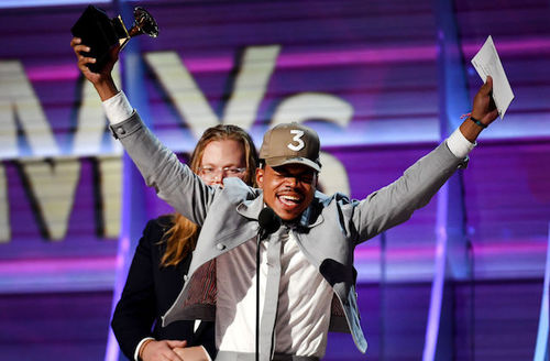 Black man in grey suit and hat hold gold and brown trophy and white piece of paper behind black microphone and in front of White man with black tuxedo and blue-lit wall