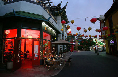 Red-lit restaurant with green awnings and grey walls near grey street in front of red and yellow lanterns and grey sky