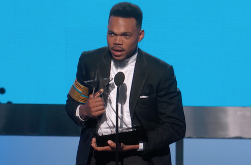 Black man in black suit and white shirt with blue, yellow and black arm band holding clear glass star awards statue behind black microphone in front of blue screen