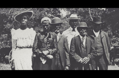 Black-and-white photo of Black women and men in formal clothing and standing in front of trees and grass