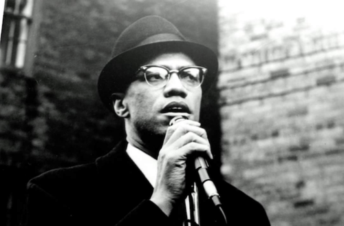 Black and white photo of black man in dark coat light hat and colorlines screenshot of malcolm x