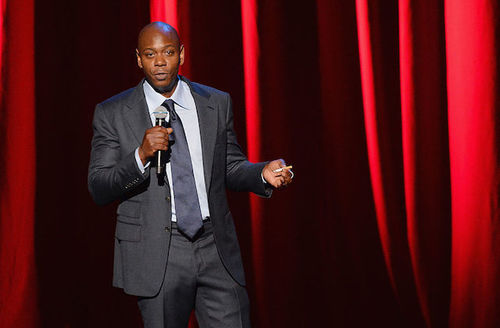 Black man in grey suit with navy tie and light blue shirt holds orange-and-white cigarette and black microphone in front of red curtain