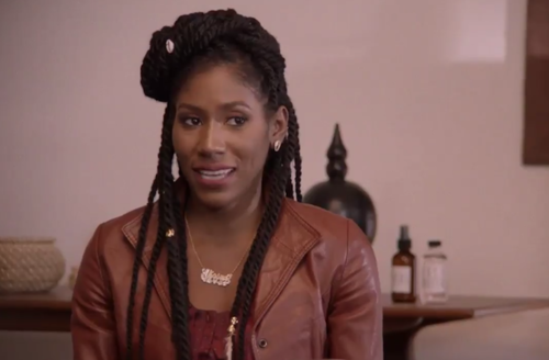 Black woman in brown shirt and leather jacket sits in front of grey wall with brown picture frame and black statuette and brown-and-black medicine containers with white labels