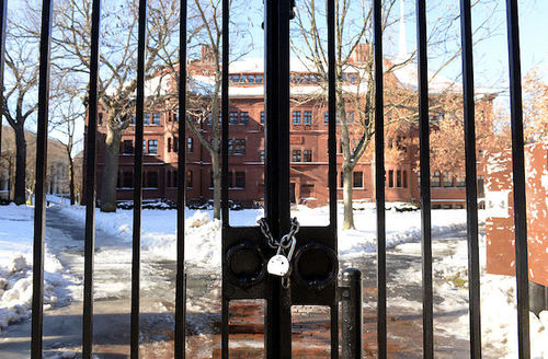 Black gate with grey lock in front of red brick building and grey and red walkways with white snow and brown trees