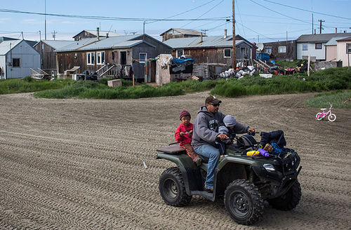 People drive ATVs along the streets of town, which sits on a barrier island in the Chukchi sea, on July 8, 2015, in Shishmaref, Alaska.