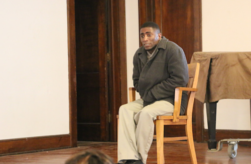 Black man in grey coat and brown shirt sits on brown chair on brown stage with white wall, brown doors and piano in yellow tarp