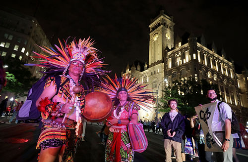 Guillermo Rosette (L) and Linda Velarde of the Chichimeca Anasazi tribe from Taos, New Mexico, join hundreds of other Native Americans and their supporters in a traditional Round Dance outside the Trump International Hotel April 27, 2017, in D.C.