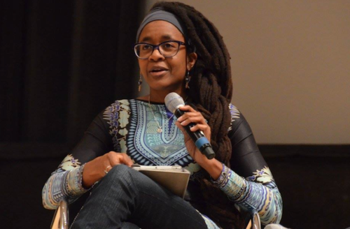 Black woman in black, purple, yellow, blue and white patterned shirt and blue jeans seated on brown chair in front of black and brown background