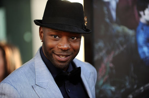 Black man in black hat and shirt with grey blazer in front of blurry yellow-lit background