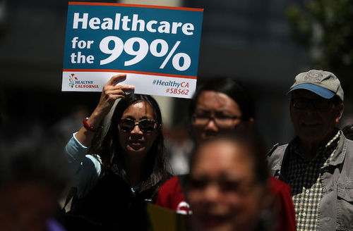 """Protestors, one holds sign that says, """"Healthcare for the 99%."""""""