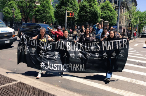 Asian women and men hold black sign with white text on grey street in front of green trees and brown and grey buildings and blue sky