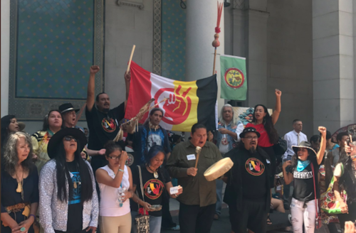 Brown people in multicolored clothing stand waving green and red-white-yellow-and-black flags on steps of building with green and white stone