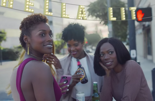 Black woman in pink dress next to Black woman in pink blazer holding brown bottle next to Black woman in dark pink dress around White table in front of yellow lights and grey city