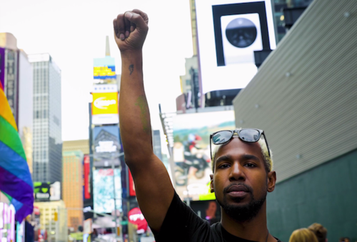 Black person with fist raised beside rainbow flag