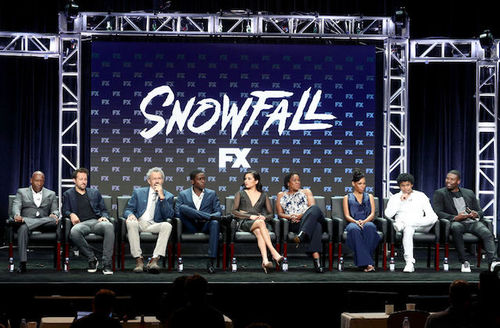 Black, Brown and White women and men sit on black stage in black chairs in front of navy screen with white letters and images and grey scaffolding