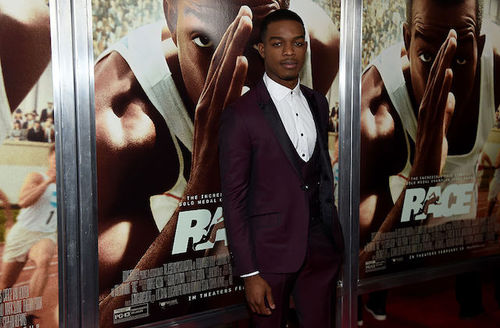 Black man in maroon suit with white shirt in front of brown-shaded movie poster with Black man's image and white text