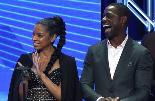 Black woman in black dress with white-lit adornments in middle stands next to Black man in grey suit in front of blue screen
