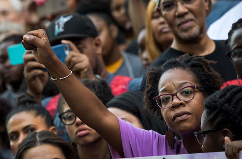 Crowd of protestors, Black woman raises her fist