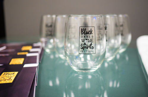 Clear glasses with black text and insignia sit on green glass table next to purple and yellow pamphlets in front of light grey wall