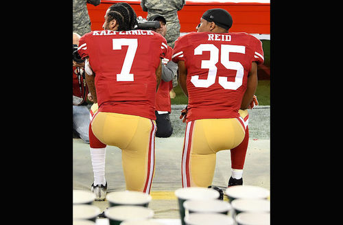 Two Black men in red jerseys with white lettering and gold pants kneel on brown tarp behind blue cups and in front of green field with red flag